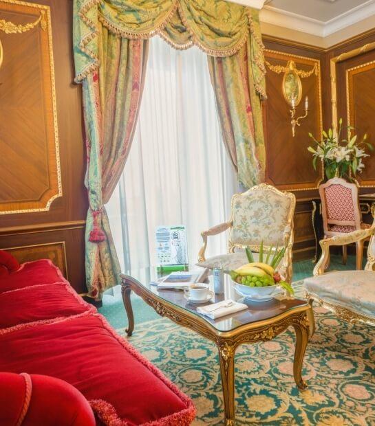 Divano rosso e tavolino nel salotto della Imperial Suite
