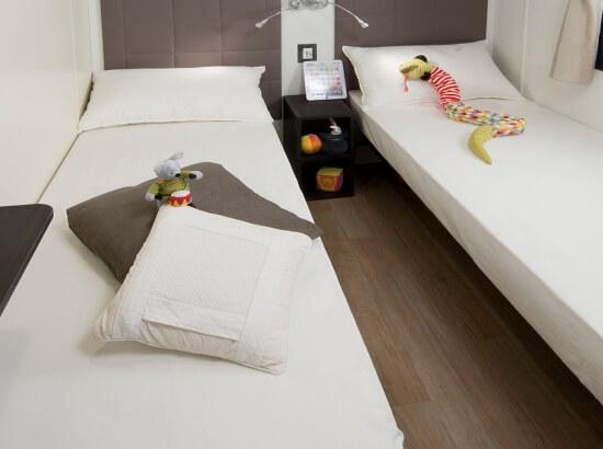 Chambre à coucher avec lits simples de la suite Paradise Suite Bay Bungalow
